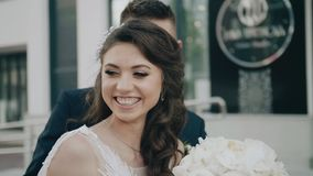 The girl turns sharply to the camera and smiles, and behind her comes her boyfriend. Happy couple in love stock footage