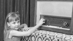 The girl turns the volume knob on the old radio. Retro style. Stock Photography