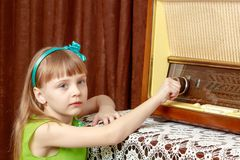 The girl turns the volume knob on the old radio. Retro style. A little girl with long blond hair and a short bangs, in a short summer dress.The girl turns the Royalty Free Stock Photos