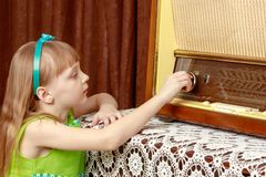 The girl turns the volume knob on the old radio. Retro style. A little girl with long blond hair and a short bangs, in a short summer dress.The girl turns the Stock Image
