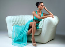 Girl in a turquoise dress on sofa Royalty Free Stock Photography