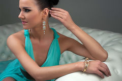Girl in a turquoise dress on sofa Stock Photo