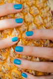 Girl with a turquoise manicure holds a ripe pineapple in her hands. Stock Photography