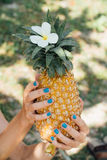 Girl with a turquoise manicure holds a ripe pineapple in her hands. Royalty Free Stock Image