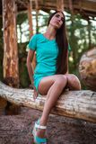 Girl in turquoise short dress sitting on a tree log stock photo