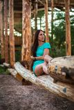 Girl in turquoise short dress sitting on a tree log stock image