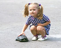 A girl with the turtle. A little girl with the turtle at summertime stock images