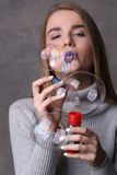 Girl in turtleneck blowing bubbles. Close up. Gray background stock image