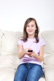Girl with TV remote control Royalty Free Stock Photos
