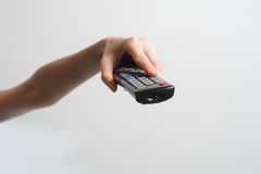 Girl with TV remote control Royalty Free Stock Photography