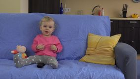 Girl with tv remote control watching television and showing true emotions. Happy interested baby child smile and surprise. Static closeup shot stock footage