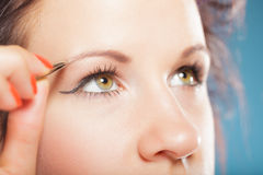 Girl tweezing eyebrows closeup Royalty Free Stock Photography