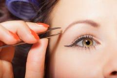 Girl tweezing eyebrows closeup Royalty Free Stock Photo