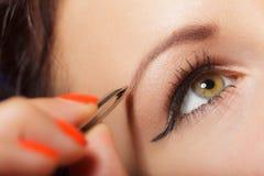 Girl tweezing eyebrows closeup Stock Photos