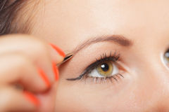 Girl tweezing eyebrows closeup Royalty Free Stock Image