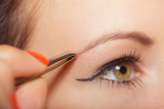 Girl tweezing eyebrows closeup Royalty Free Stock Photos