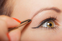 Girl tweezing eyebrows closeup Royalty Free Stock Photography