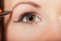 Girl tweezing eyebrows closeup Stock Image