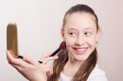 Girl twelve years with pleasure face powders Stock Photos