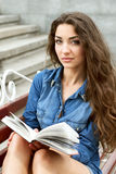 Girl of twenty reads a book while sitting on a bench Royalty Free Stock Photos