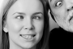 Girl is twisted. Girl and man squinting eyes on silly faces Stock Photography