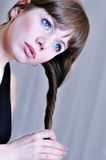 Girl   twisting hair. Lovely girl  twistinging her long hair over the gray Stock Image