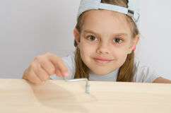 Girl twists the screw with an Allen key Stock Images
