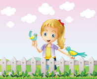 A girl with two birds near the wooden fence Stock Photo