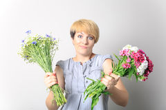 Girl with two bouquets of wild flowers posing in Studio. Solution. Choice. Royalty Free Stock Photography