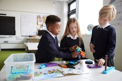 A girl and two boys standing at a table in a primary school classroom working together with toy construction blocks, close up royalty free stock photos