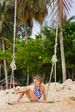 Girl with two braids in a bathing suit on a swing on the beach Royalty Free Stock Photo