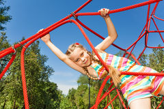 Girl with two braids hangs on ropes of red net Royalty Free Stock Photo