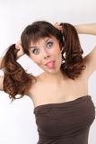 Girl with two braids show tongue Royalty Free Stock Photography