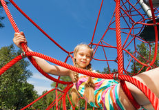 Girl with two braids sits on ropes of red net Royalty Free Stock Photos