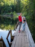 A girl with two children are standing on the old wooden bridge across a quiet river stock image