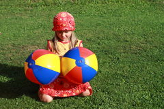 Girl with two colorful balls. Little girl in red and yellow dress kneeing with colorful balls royalty free stock images