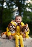 Girl with two dogs shih tzu. The girl in the yellow jacket. Dogs in yellow clothes. Girl walking with a dog. Girl with two dogs shih tzu. The girl in the yellow royalty free stock image