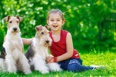 The girl and two fox terriers. The little girl with two dogs of breed fox terrier on a green lawn Royalty Free Stock Photos