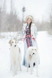 Girl with two greyhounds walking in winter stock photos