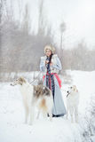 Girl with two greyhounds walking in the winter. Beautiful girl with two greyhounds walking in the winter Stock Photography