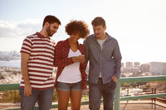 Girl and two guys reading messages. A girl and two guys reading a message on a cell phone while standing against a railing with a city scape behind them Stock Photo