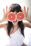 The girl and  two half of grapefruit Royalty Free Stock Photo