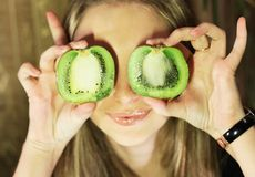 Girl and two halves of kiwi Royalty Free Stock Photo