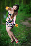 Girl with two halves of orange. Beautiful girl in the woods with two oranges stock image