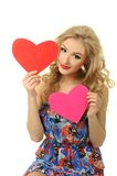 Girl with two hearts. Pretty blond girl in red dress make choice between two hearts Royalty Free Stock Image