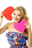 Girl with two hearts. Pretty blond girl in red dress make choice between two hearts Stock Photos