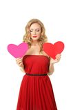 Girl with two hearts. Pretty blond girl in red dress make choice between two hearts Royalty Free Stock Photos