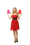Girl with two hearts. Pretty blond girl in red dress make choice between two hearts Stock Image