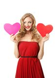 Girl with two hearts. Pretty blond girl in red dress make choice between two hearts Royalty Free Stock Photo