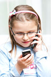 Girl with two mobile phones. Portrait of young girl talking and text messaging on two mobile telephones Royalty Free Stock Photos